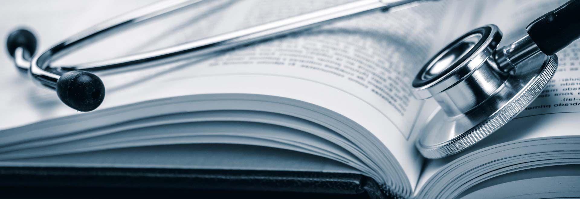 Ein Stethoskop liegt auf einem Buch