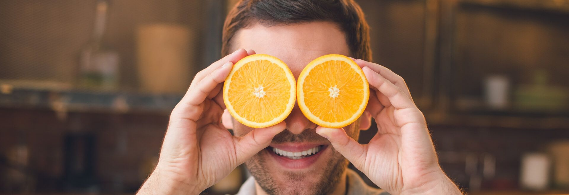 Ein Mann hält sich zur Veranschaulichung für gesunde Ernährung zwei Orangenhälften vor die Augen