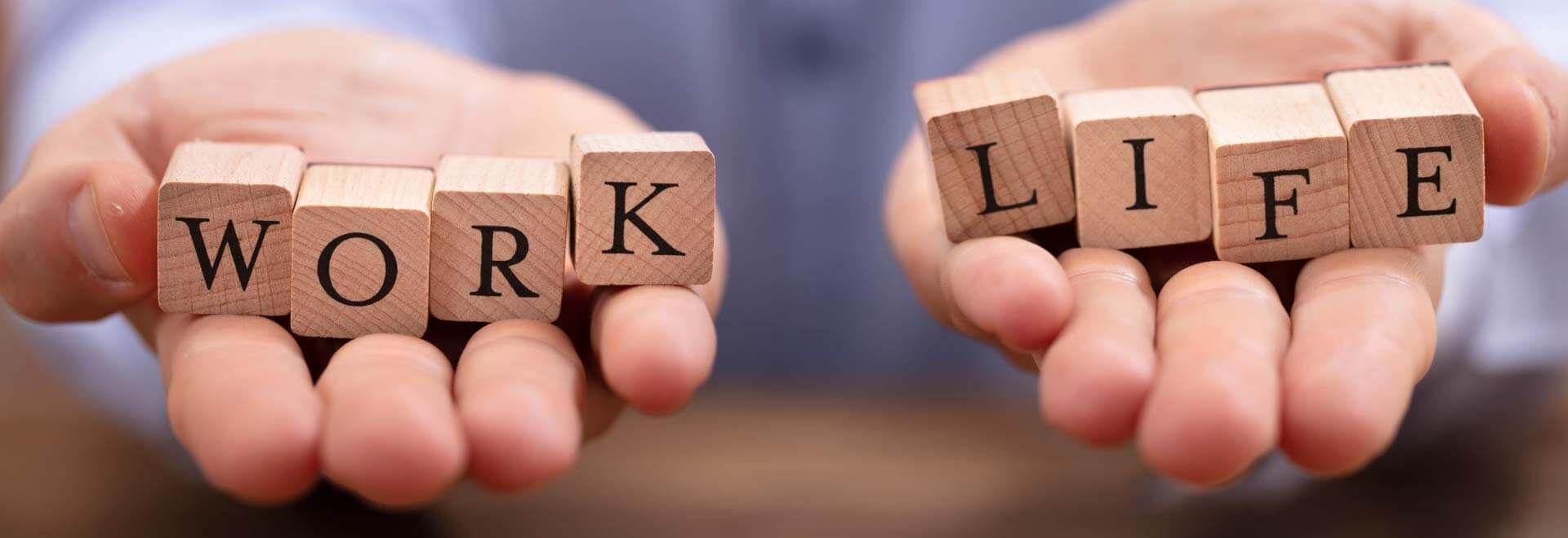 auf zwei Händen liegen Buchstabenwürfel mit den Worten work life