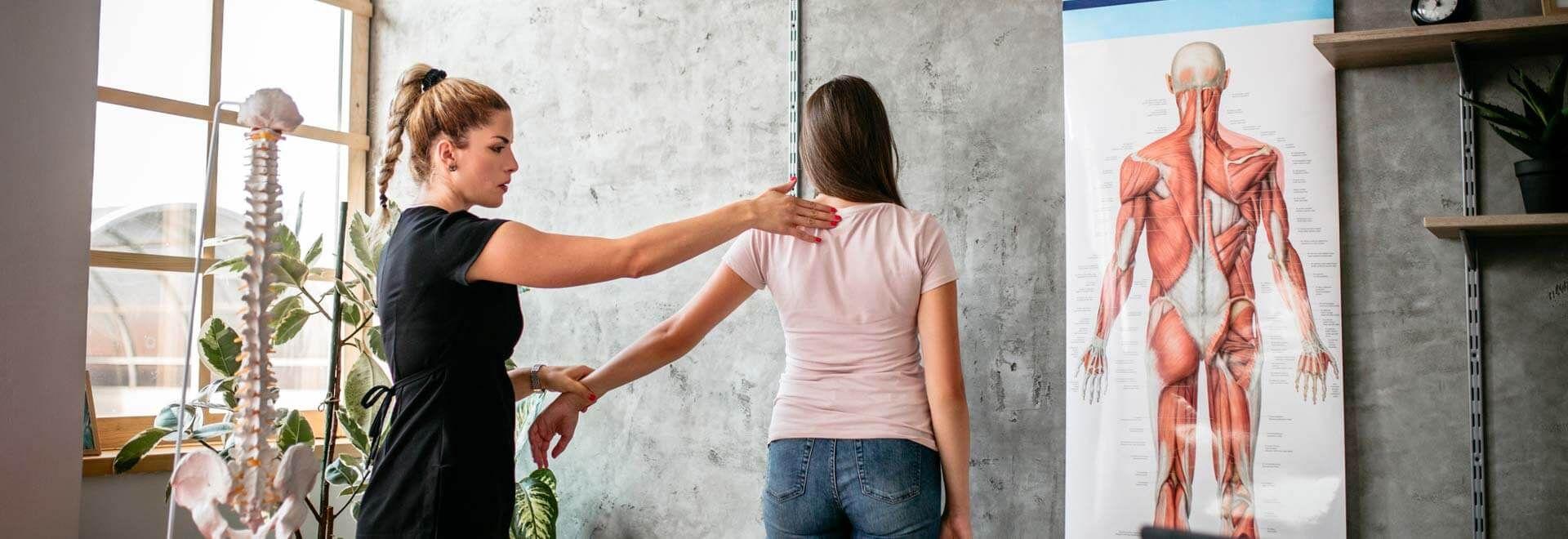 Eine Rückenschullehrerin kontrolliert die Haltung einer Klientin